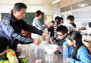 幸松伝司さん(左)の指導を受け、マイエンザを作る児童=伊万里市の伊万里小学校