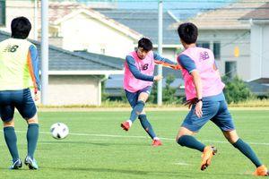 磐田戦に向けた練習で、シュートを放つMF安庸佑(中央)=12日、鳥栖市北部グラウンド