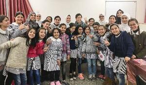 国連パレスチナ難民救済事業機関の学校で、子どもたちと写真に納まる吉田美紀さん(奥中央右)=2019年1月、パレスチナ自治区ガザ(吉田さん提供・共同)
