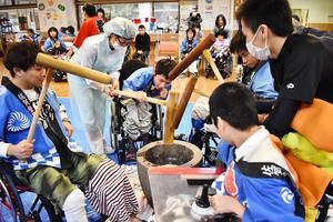 息を合わせながら餅をつく利用者たち=佐賀市の佐賀整肢学園こども発達医療センター