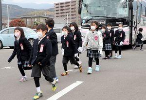 バスから降り、避難所に向かう玄海みらい学園の児童=正午すぎ、ゆめぷらっと小城