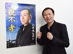 気合いの入ったポスターの横でポーズを取る六本木ヒロシさん=佐賀新聞社唐津支社