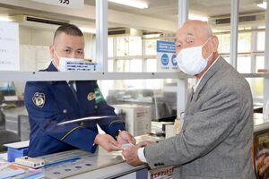 有田幹部派出所の岡本新所長(左)から運転経歴証明書を受け取る井上萬二さん=有田町の同派出所