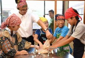 みそ作り体験で、大豆をもむ参加者ら=佐賀市の赤松公民館