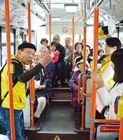 コミュニティーバスの車内で岩崎数馬さん(左)の案内を聞く参加者=有田町