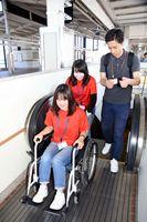 車いすでエスカレーターを体験する学生たち=武雄市のJR武雄温泉駅