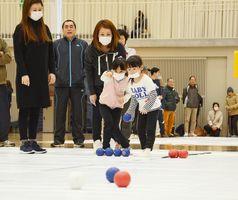 白の目標球に向けて狙いを定める子ども=嬉野市社会文化会館リバティ