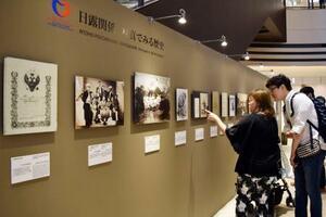写真展「日露関係 写真でみる歴史」の展示を見る人たち=14日、東京都千代田区