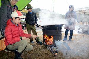 炊き出し訓練をするボーイスカウトと「話輪の食楽クラブ」のメンバー=有田町の菅野公園