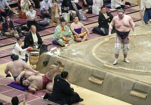大相撲秋場所11日目の22日、照ノ富士(右)に寄り切りで敗れ、土俵下に落ちた高安=両国国技館