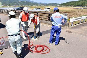牟田辺遊水地(奥)の運用に備え、域内を通る道路の入り口を封鎖する手順を確かめる関係者=多久市南多久町