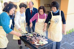 肉や魚を焼く更生保護女性会のメンバーら=佐賀市長瀬町の佐賀県恒産会