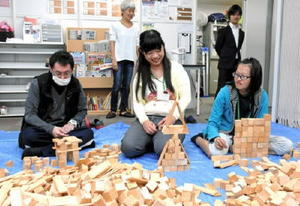 ヒノキ間伐材の積み木で思い思いの作品づくりに挑戦する利用者=佐賀市のユニカレさが