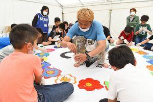 アーティストのミヤザキケンスケさんとテントに色とりどりの花の絵を描いた仁比山小の児童たち=吉野ケ里歴史公園