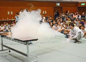 液体窒素でアルコールランプを消す科学実験。子どもたちは真剣に見入った=佐賀市のメートプラザ佐賀