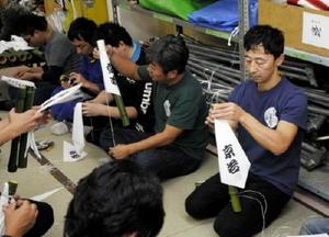 集会場で采配作りに取り組む波多江健さん(右)。唐津くんちは「チームワークの理想」と語り、準備段階から携わる=唐津市京町
