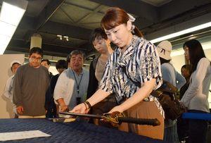 日本刀を両手で持ち、重さを実感する来場者たち=佐賀市の県立博物館