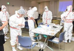 正しい手順で防護服を身にまとった参加者たち=鹿島市生涯学習センター「エイブル」