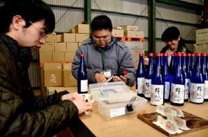 「絆伝心」のラベル貼りをする「ユニカレさが」の学生と職員たち=みやき町の天吹酒造