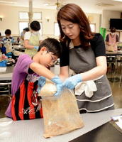 米こうじと塩を合わせたものを、つぶした大豆に混ぜる参加者=佐賀市高木瀬西の佐賀大和工業団地