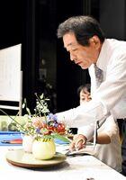 「おもてなしの心」を表現する作品を、ステージ上で披露する中村福宏教授=佐賀市天神のアバンセ