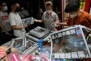 24日、香港で廃刊する蘋果日報の最後の新聞を買い求める人々(AP=共同)