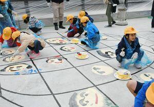 橋の床となる面にペンキで自分の顔を描く児童たち