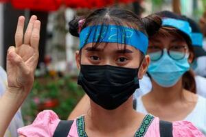 12日、ミャンマー・ヤンゴンで、抵抗を示す3本指を掲げて国軍に抗議するデモ参加者(AP=共同)