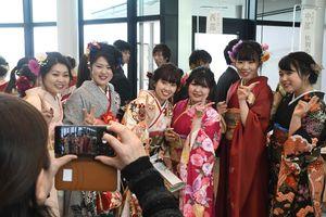 友人との再会を喜び合い、記念写真を撮る新成人ら=神埼市千代田文化会館「はんぎーホール」