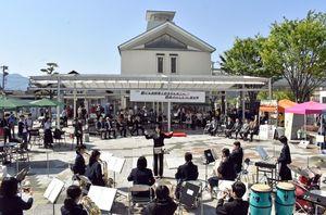 伊万里市駅ビルのリニューアルを祝う式典で演奏する伊万里中吹奏楽部(手前)=同市の駅前公園