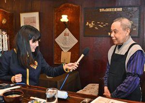 店主の橋本末広さん(右)に話を聞くNBCラジオ佐賀の山田菜穗さん=佐賀市のコーヒーはしもと