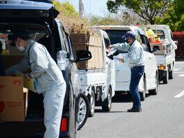 ごみを持ち込もうと車列をつくる利用者に積み荷の内訳などを確認する職員=10日午前11時ごろ、佐賀市高木瀬町の市清掃工場