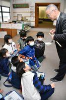 市民学芸員から、分銅を使った重さの量り方を教わる芦刈観瀾(かんらん)校の児童たち=小城市立歴史資料館