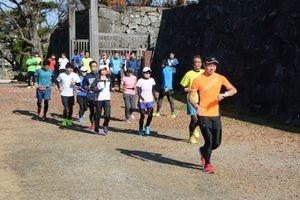 コーチに先導されながらランニングをする参加者=佐賀市の佐賀城跡
