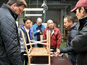 試作品の出来栄えを確かめるガブリエル・タンさん(左から2人目)と平田尚士社長(中央)ら=佐賀市諸富町の平田椅子製作所