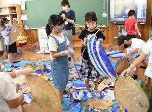 相知くんちの山笠で使う野面の張り替え作業をする子どもたち=唐津市の相知小