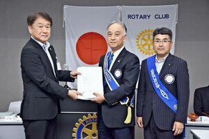 大野敬一郎小城市教育長(左)に図書カードの目録を手渡した小城ロータリークラブの田中博起会長(中央)=小城市のゆめぷらっと小城