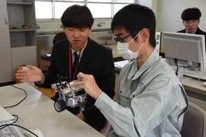 ロボットの動きを確認する生徒たち=佐賀市の佐賀工業高校