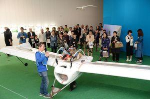 「M-02J」の仕組みなどを解説する八谷和彦さん(手前)=佐賀市の県立美術館