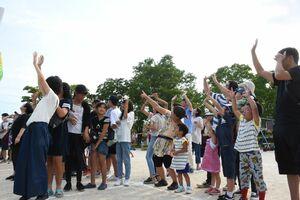 空撮するドローンに向かって手を振る参加者たち=唐津市鏡の鏡山小学校