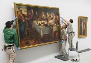 「バロック展」開幕を前に、絵画を慎重に飾り付けるスタッフ=佐賀市の県立美術館