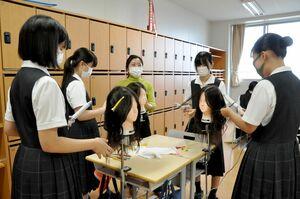 卒業生の手ほどきを受けてヘアアイロンで巻き髪に挑戦する生徒たち=佐賀市の佐賀女子高