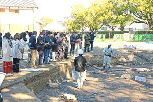 発掘調査現場の説明を受ける参加者=佐賀市の佐賀城本丸歴史館南側