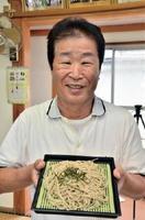 自慢の五割そばを紹介する、東尾蕎麦の会会長で区長の宮原善昭さん=みやき町の東尾公民館
