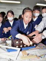 冷え固まったろうそくを型枠から取り出す児童=みやき町の中原小学校