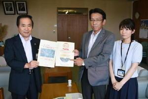 塚部芳和市長にDVDを手渡す渕上康児社長。右は番組を制作した福田千春さん=伊万里市役所