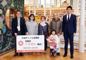 来場10万人目となり、小松市長(右)や家族と一緒に記念写真に納まる小嶋紗英ちゃん(右から3人目)=武雄市のこども図書館