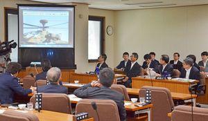 陸自のAH64D戦闘ヘリコプターが神埼市の民家に墜落した事故について、中間報告の内容を佐賀県議会特別委員会で説明する防衛省関係者(右奥)=県議会棟