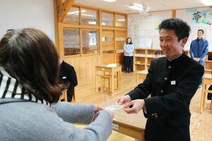 受験生向けの「落ちない葉」のしおりを受け取る生徒=佐賀市の富士中