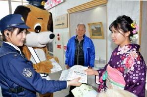 犬のおまわりさんのマスコットとともに、新成人に飲酒運転防止などを呼びかける東尾交番の署員=みやき町コミュニティーセンターこすもす館